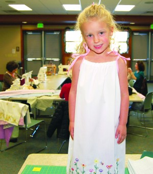 "READY FOR THE CATWALK — Liv Bess, 4, models a pillowcase dress created during the first ""Dress A Girl Around the World"" sewing bee last Wednesday at the El Dorado Hills library. The dresses go to girls ages 4 to 12 who live in Third World countries.Village Life photo by Mike Roberts"