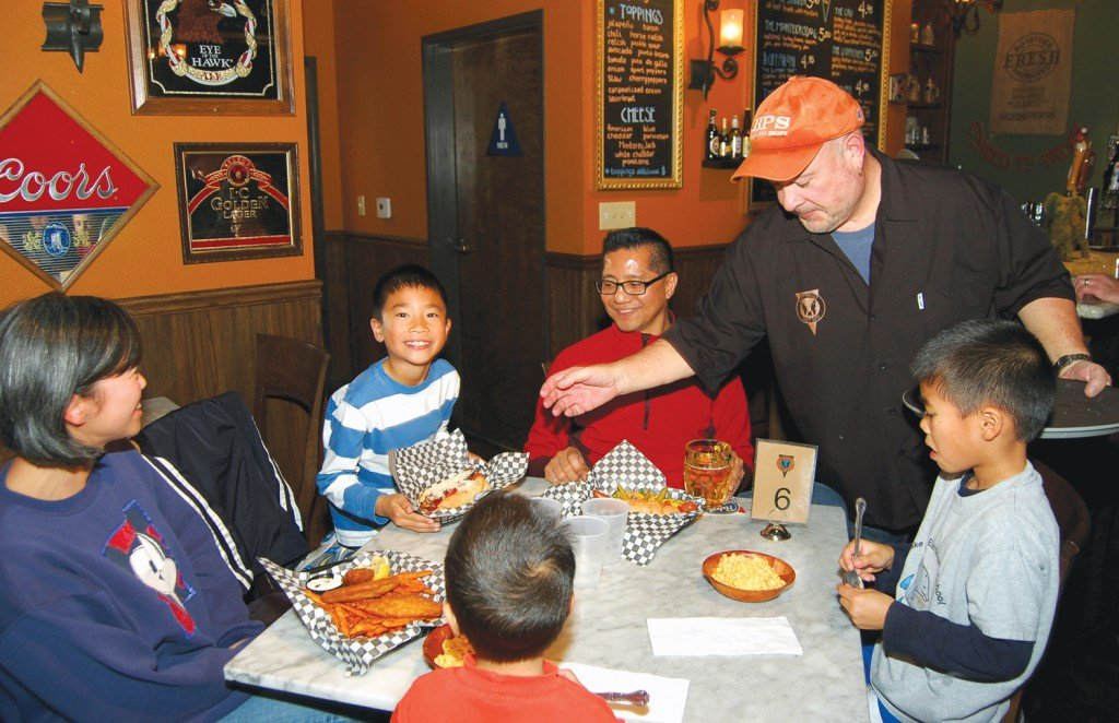 "SECOND-TIMERS — Jim O'€™Donnell, father of Ruffhaus Hot Dog brothers Fred and Chuck Knight, serves up some mac and cheese, Chicago dogs and fries to El Dorado Hills Medina family, who ate two meals at the innovative hot doggery on Friday. Left to right, mom Sharon, Joshua, 8; dad Max, Mathew, 5; and Gabriel, 3, with his back to the camera. How's the food? ""Best dogs in town,""€ says Max. Village Life photos by Mike Roberts"