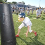 Jake Hoffman, 9, from El Dorado Hills goes through a tackling dummy drill at the football camp held at Oak Ridge. Village Life photo by Pat Dollins
