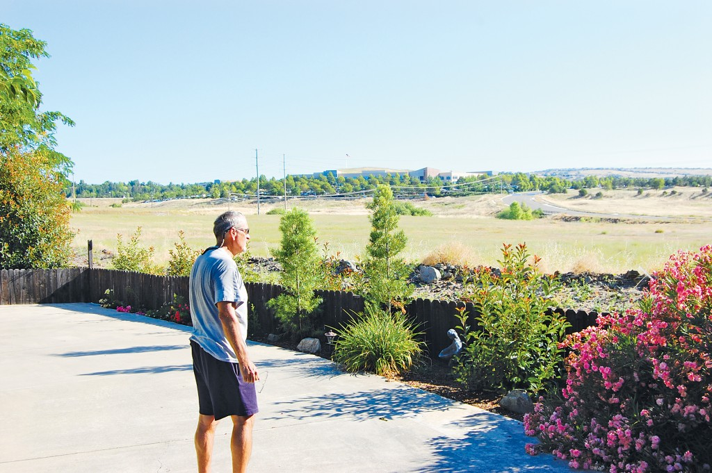 BED BATH AND BEYOND? — Springfield Meadows resident Terry Thomas stands in his driveway and ponders the future of the neighboring, mostly vacant Town Center West site which could become home to large retail stores under a pre-application recently filed by the Mansour Company. Village Life photo by Mike Roberts