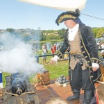 PIRATES EVERYWHERE — Capt. MacLaren, left, fires off the cannon aboard the HMS Dauntless, an 80-foot armed merchant ship on wheels parked at Village Green Park Saturday. The pirates' visit raised money for the El Dorado Hills Library.  Village Life photo by Shelly Thorene