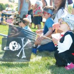 LITTLE PIRATE —  Lillyann Hinsz, 2, (parents, Brent and Linda) of El Dorado Hills holds a pirate flag as she watches the sword fighting. Village Life photo by Shelly Thorene
