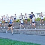 CHEERING ON — The Jr. Trojans Midget Cheerleaders encourage runner Carlie Broadhurst. Courtesy photo