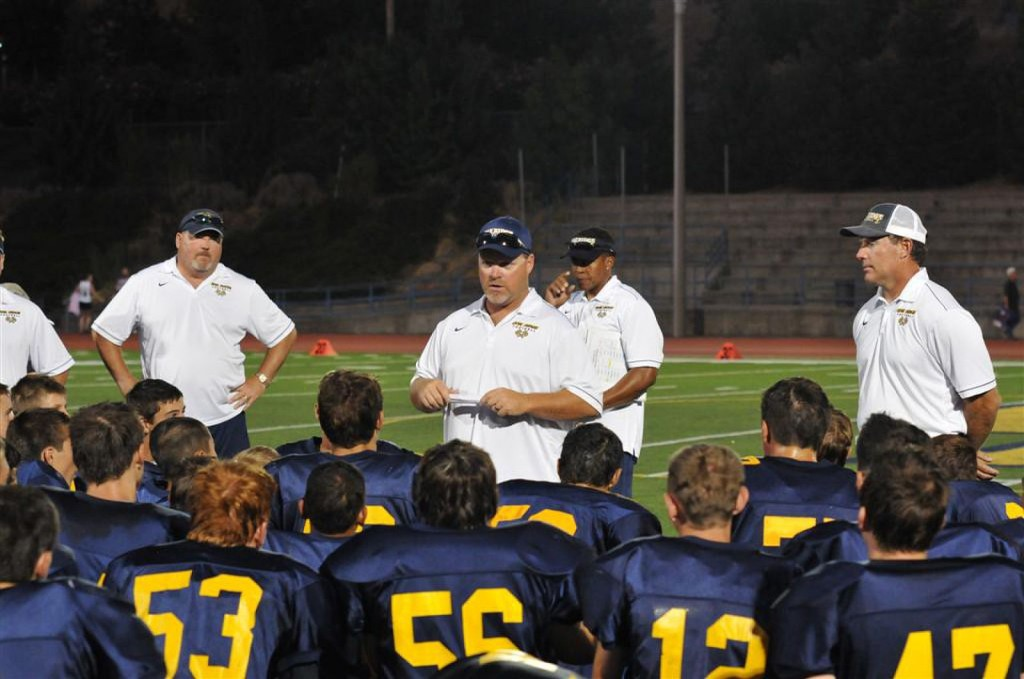 COACHES AND PLAYERS talk strategy during the freshman football game against Cordova. Photo by Suzanne Hunt