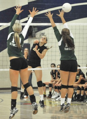 Lady Bruins Layne Davidson (No. 17) and Lianna Sybeldon (No. 10) try to block a kill sent over by Lady Trojan Mysha Davies during the contentious match. Village Life photo by Pat Dollins