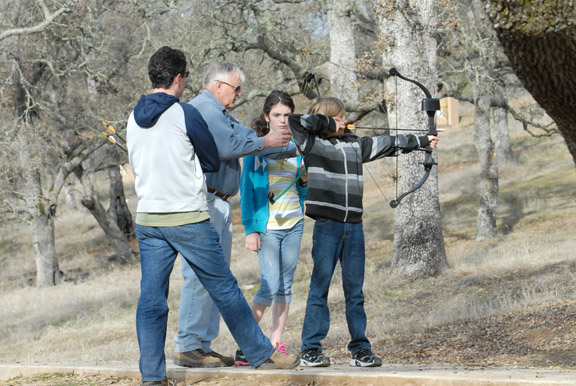 El Dorado Hills Bowmen President Tom Grube, 69, of El Dorado Hills, second from left, supervises Kieran Gallagher, 11 of Danville, right, and Mallory Cash, 11, of Cameron Park as they prepare to use their compound bows at El Dorado Hills Bowmen archery range on El Dorado Hills Boulevard in El Dorado Hills. Also pictured, Mallory's father, Bryan Cash, 43, of Cameron Park. Village Life photo by Shelly Thorene