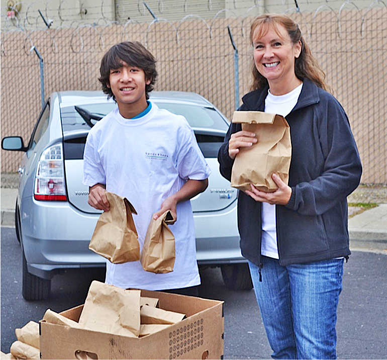 Inga Buckendorf, an adult lead with Hands4Hope, hands out meals to the homeless with youth volunteer Daniel Jamieson. Courtesy photo