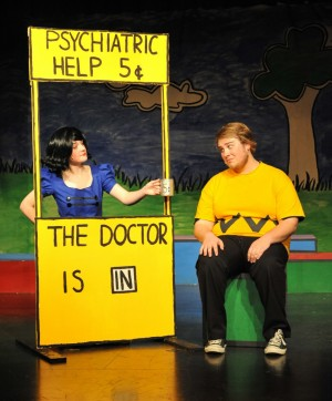 Lucy (Hannah Christiansen), left, requests a 5 cent payment after a psychiatric session with Charlie Brown (Matt Howlett.) Village Life photo by Pat Dollins