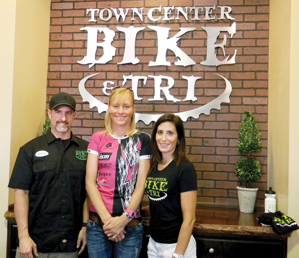 Town Center Bike & Tri owners Wilson and Erin Gorell welcome triathlete Michellie Jones, center, who flew in from San Diego for the El Dorado Hills shop's grand opening Saturday. Village Life photo by Noel Stack