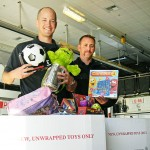 El Dorado Hills firefighters Chris Landry, left, and Mike Gygax hold up some toys already donated to this year's Toys for Tots campaign. In early December Landry said he hopes to see thousands of toys in the Station 85 engine bay. Village Life photo by Noel Stack