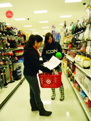 Interact Club volunteers Uma Dingankar and Ashlee Gonzales pick out a bouncy ball for a little boy during the Adopt A Family shopping trip at Target Friday. Village Life photo by Noel Stack