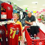 JUST MY SIZE! - Joseff Johnson, 11, of Placerville holds up a 49er's jersey to check the size while shopping with Big Brother Glen Ingram of Diamond Springs. More than 170 children were treated to a Target shopping spree and Rotary pancake breakfast during the Snowball Holiday Shopping event Saturday morning in El Dorado Hills. Village Life photo by Shelly Thorene