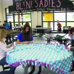 Hands4Hope volunteers make blankets in Oak Ridge's cafeteria. The warm and cozy fleece throws will be donated to local seniors. Photo by Samita Dutta