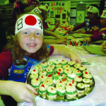 Girl Scout Kaitlyn Shedd shows off Japanese sushi (sort of). The sushi served at World Thinking Day was made with rice krispy treats, gummy fish and green fruit wrap in place of seaweed.  Photo by Julie Samrick