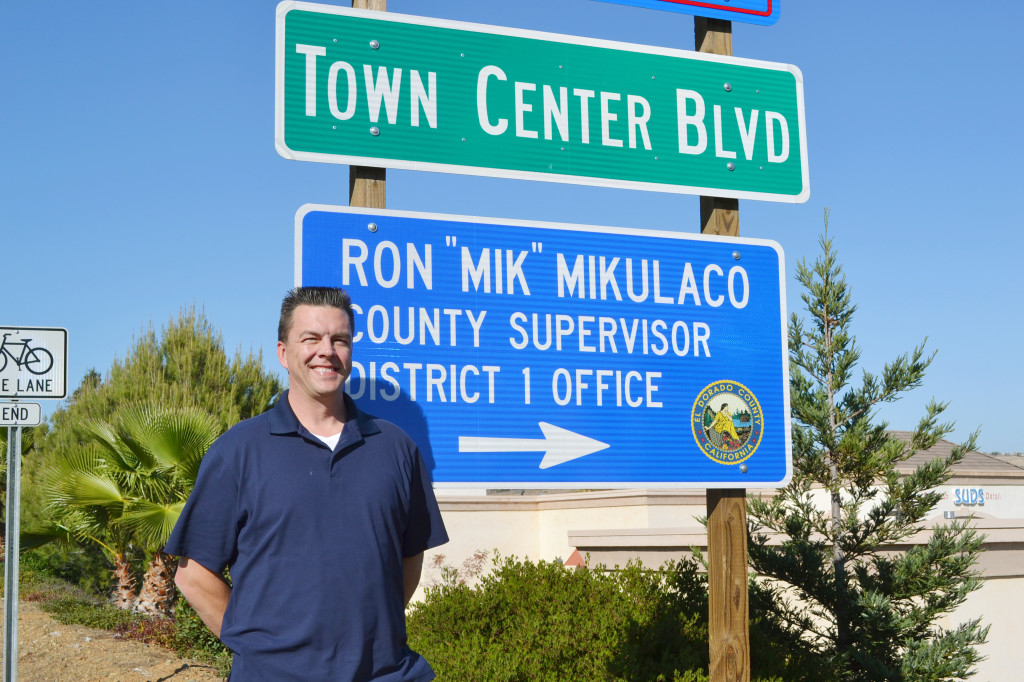 Supervisor Ron Mikulaco stands by the sign directing constituents to his new satellite office. Village Life photo by Julie Samrick