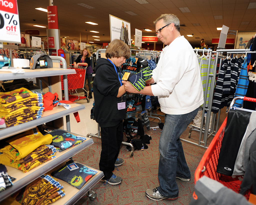Big Brother Mark Bassler of El Dorado Hills, right, has some fun helping his Little Brother Jason Slife, 12, of Cameron Park try on gloves at the Snowball Shopping Spree at Target Saturday morning. Village Life photo by Shelly Thorene