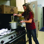 In the kitchen, Ashely Abraham, 17, dishes up the garlic butter for the crab.