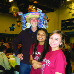 Rotary Club of El Dorado Hills President Coy Baugh and Interact volunteers Michelle Dutta, 17, and Sydney Simon, 16, left to right, pause for a photo before getting back to the important business of selling raffle tickets for Coy's stylish Scratcher Hat at the club's 21st annual Crab Feed & Dance Saturday night.  Village Life photo by Noel Stack