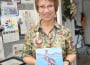Artist Lori Anderson stands in her studio holding a ceramic tile imprinted with her painting of a pelican. Village Life photo by Shelly Thorene